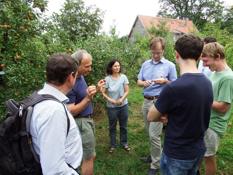 Excursion to Arboretum Bielefeld in 2019 (group listening to a talk while standing between apple trees)