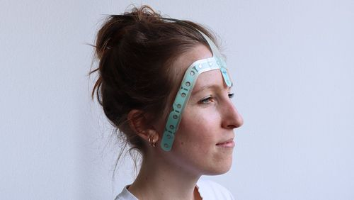 A young woman carries the new EEG measuring device