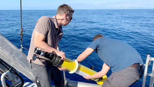 Two men stand at the stern of a ship and throw the yellow, elongated buoy into the sea.