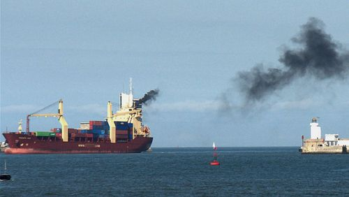 Cargo vessel emitting black exhaust gases to the air.