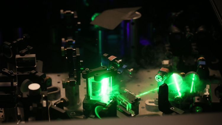 A green laser beam is guided by mirrors and lenses through an experimental set-up.