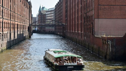 A view of the Speicherstadt warehouse district and a sightseeing boat in the foreground.