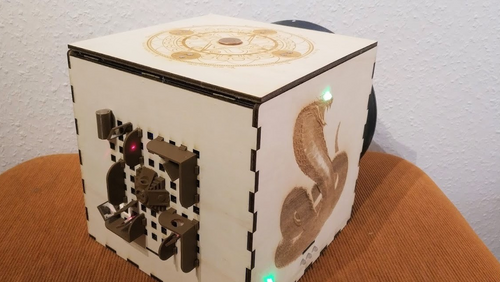 Edge view on a wooden cube. On one side, there is an image of a cobra, on the other a sun wheel, on the third plastic models of Aztec buildings. Not to be seen is the fourth side with a vault opening.