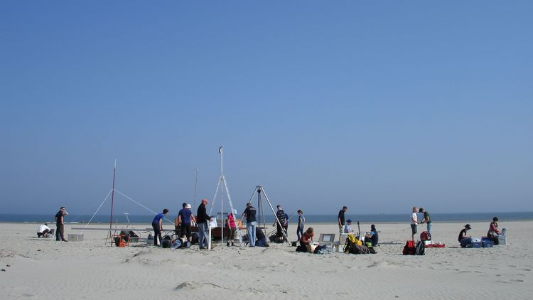 Many people perform measurements on a sandy beach.