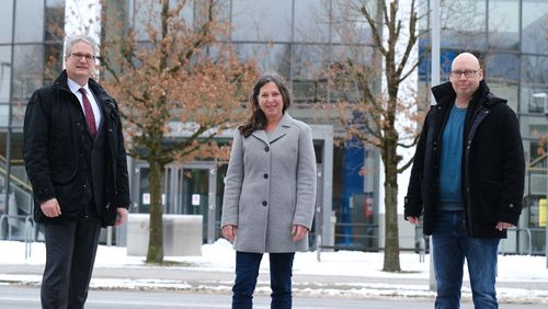 three persons in front of the university